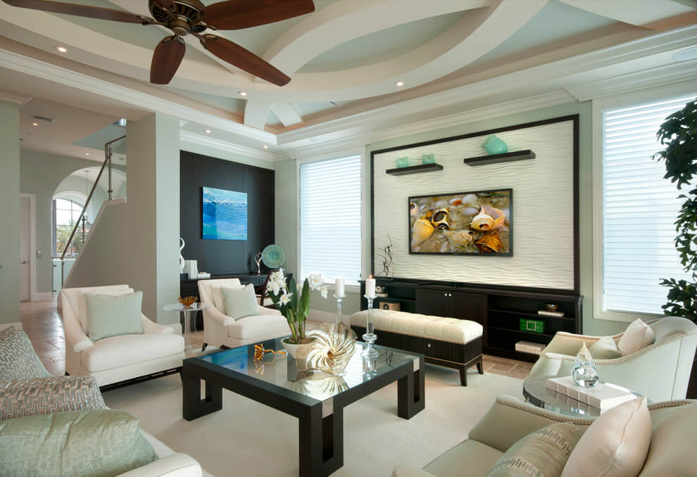 Living rooms ceiling fans made out of dark wood. A classical bland of white and black furniture sets with a central magazine table and withe rug that covers the tile like flooring.