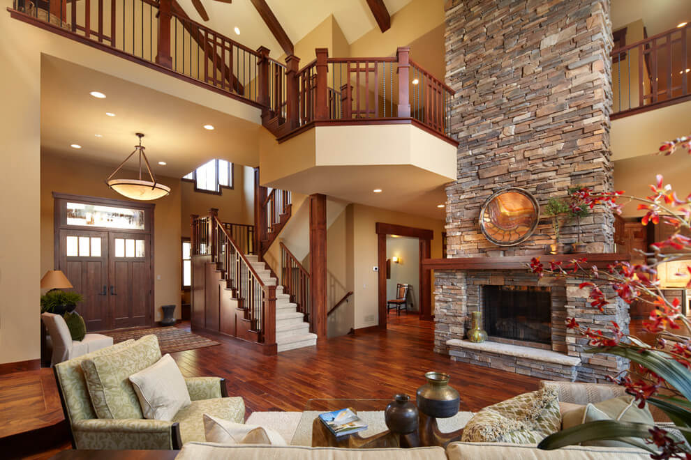 Living rooms stone fireplaces with small entryway or mudroom. Interior staircase that leads to the second floor. Also dark wood insertions on the hardwood flooring.