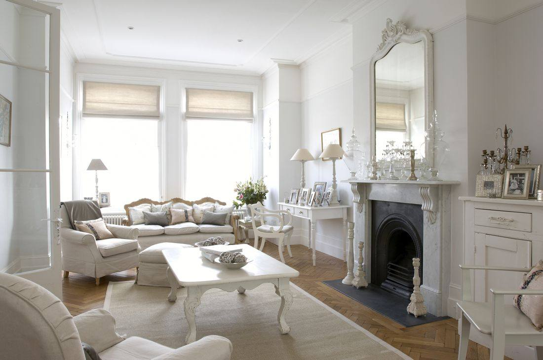 Exclusive living rooms white furniture - A white mirror with white frame is on top of the dark blue fireplace. A white rug is covering the natural looking hardwood floor.