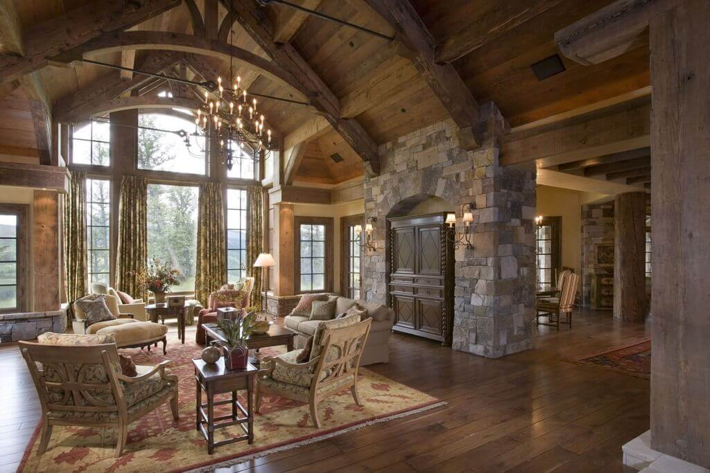 Living rooms with area rugs inside a beautiful mountain cottage made out of stone and wood. Larges arches that are binding to the V shaped ceiling. Also three chairs and a large sofa.