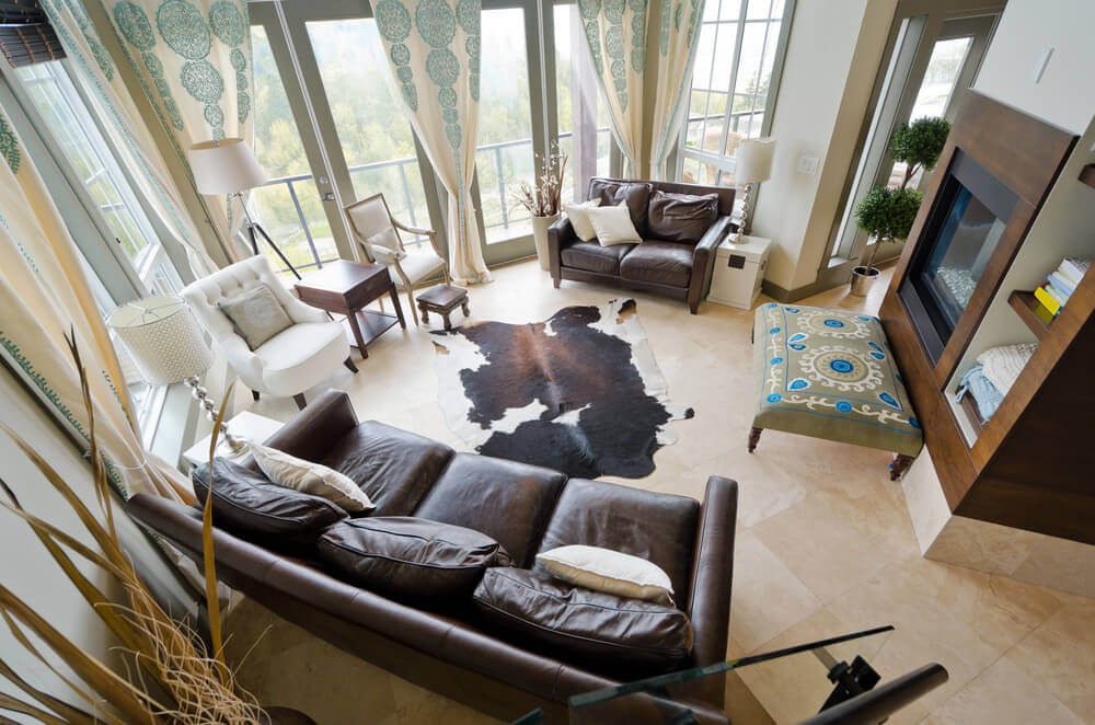 Living rooms with end tables - An overview of a room with small balcony and plenty of windows. In the center there is a cow rug and a small ottoman with floral patterns.