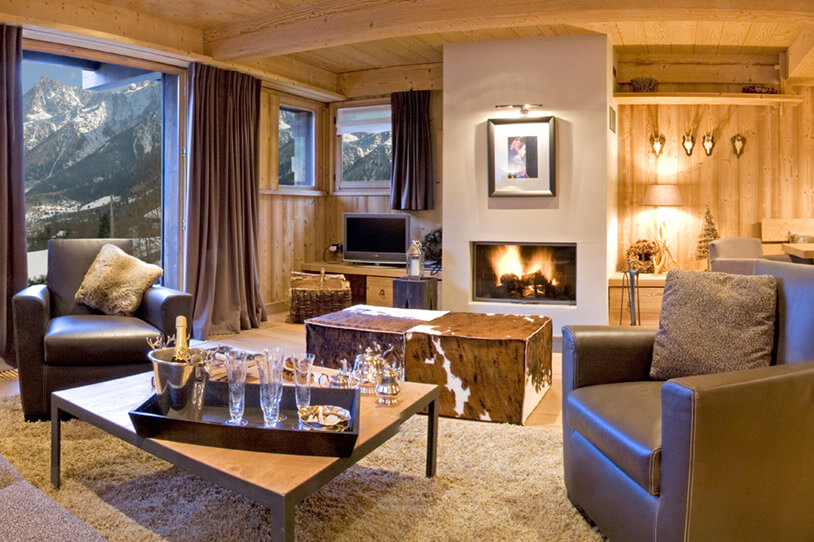 Luxurious cozy living rooms design ideas with beautiful view overlooking the mountains. This cottage has an unique design with wooden walls and metallic tea table.
