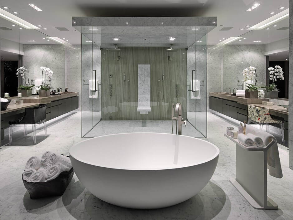 Luxury white bathroom designs - this unique set of central shower that has three sided made of glass and a white circle bathtub in contrast with the black furniture and chair.