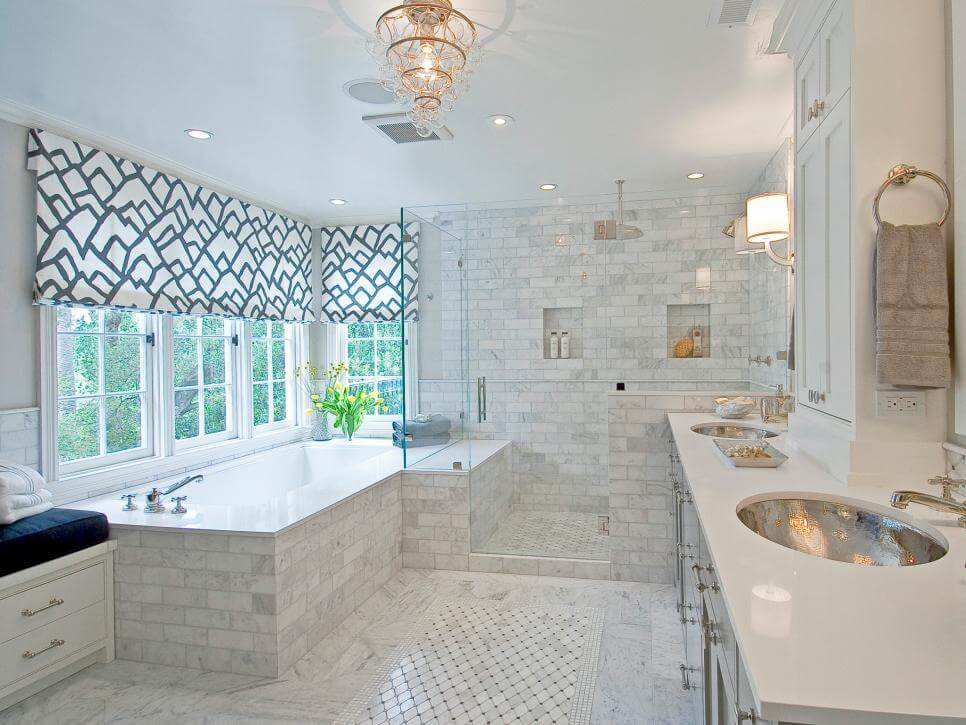 Master bathroom window ideas - A cozy designed room with two golden sinks and white bricks marble bathtub and shower. Also the bathroom has a small chandelier.