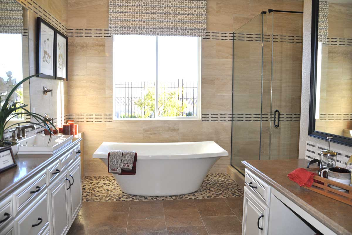 Master bathrooms with free standing soaking tubs with walls that have a patterned designed made out of black and beige small tiles. A small shower cabin and small windows.