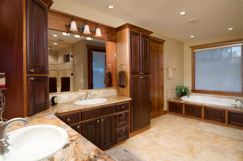 Master bathrooms woodwork furniture, dark and neutral looking wood cabinets with large ans small drawers, also a large single mirror and two white sinks.