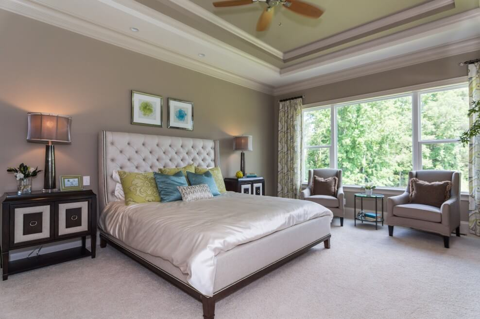 A luxurious master bedroom with high ceiling design, a king size master bedroom with a white headboard and made out of leather. This is in perfect contrast with the bed feet that are made out of dark wood.