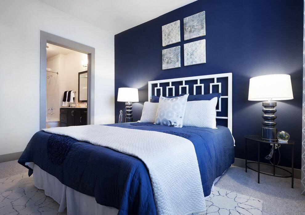 Inspired from a Marina Bay motif, this master bedrooms with blue walls has a very worm look despite the cold blue color that covers a wall. In contrast with the white sheets and bed pillows.