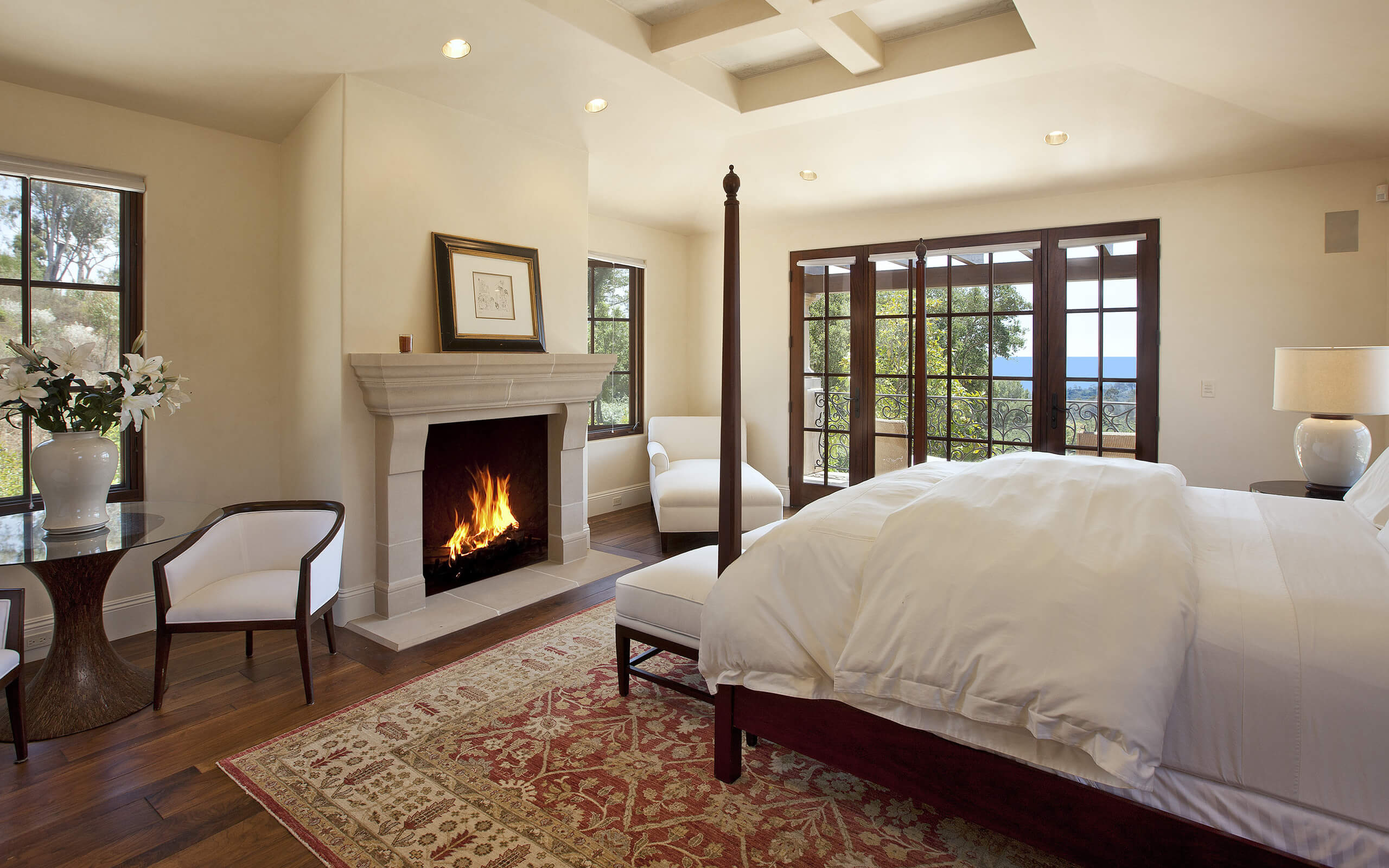 A modern approach to master bedrooms with fireplaces. In this photo is a stone made fireplace with white chairs, white bed cover sheets, and a colorful rug.