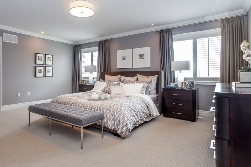Nice looking design of a master bedroom with gray walls and a grey loveseat, in contrast with the beige carpet, drapes, and dark wood furniture, cabinets with storage.