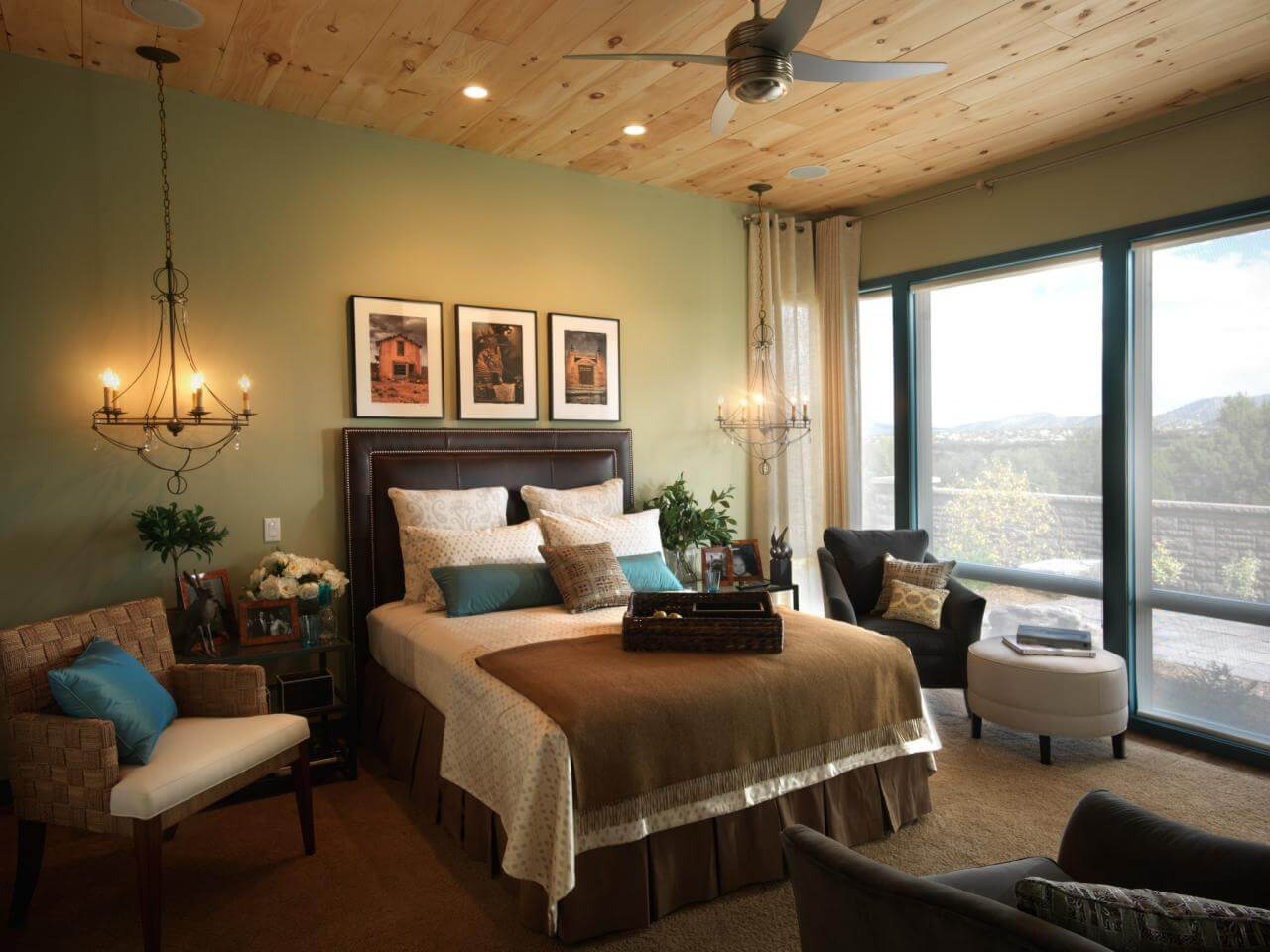 Great master bedrooms green walls with earth tone color of the fabrics that covers the master bed, the chairs and the carpet. Also a light wood ceiling that has a 4 propeller fan.