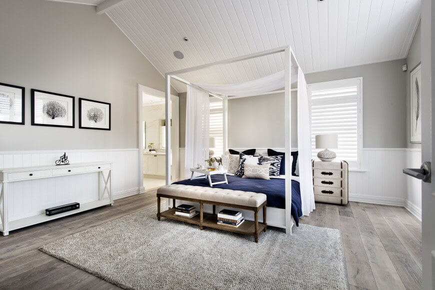Impressive master bedrooms with light wood floors that in tone with the light grey rug, the white ceiling and also the white furniture. There is a white loveseat that has a storage under nit.