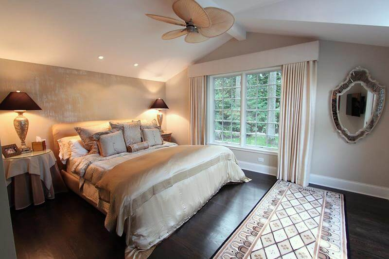 Cozy master bedrooms with dark wood floors, a modern patterned white and black rug near the beige master bed. Two large lamps near the bed and a ceiling fan.