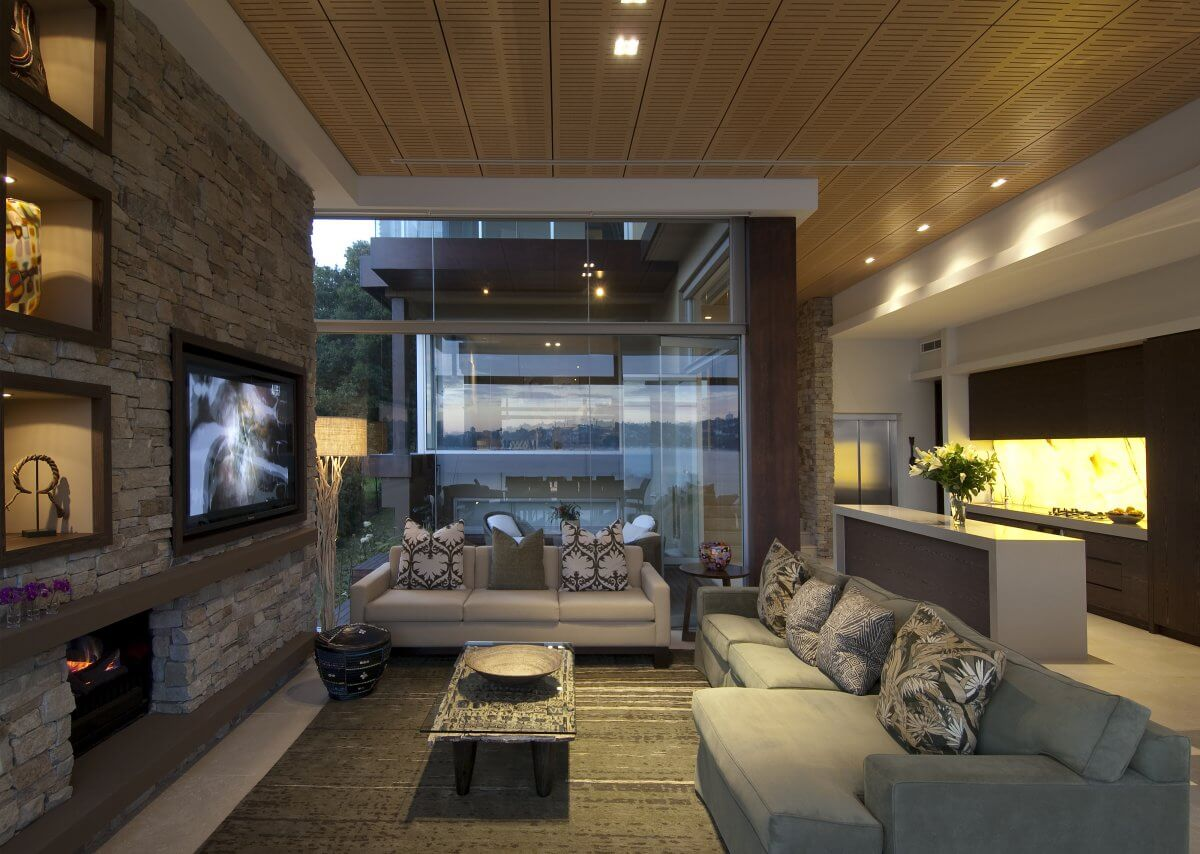 Modern living room designs with fireplace made out of bricks and integrated TV into the bricked wall. Large glass wall and tow sofas with multi floral pillows.