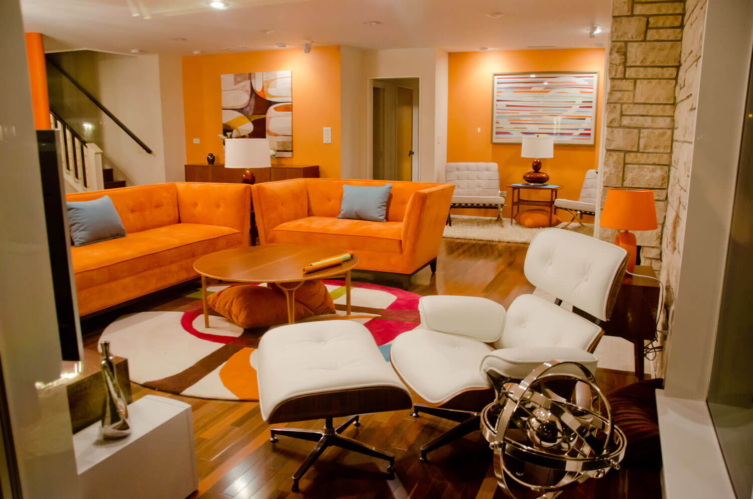 Orange living room ideas with orange walls, orange sofas, orange lamps and round coffee table. In contrast with the white relaxation chairs and white ceiling.