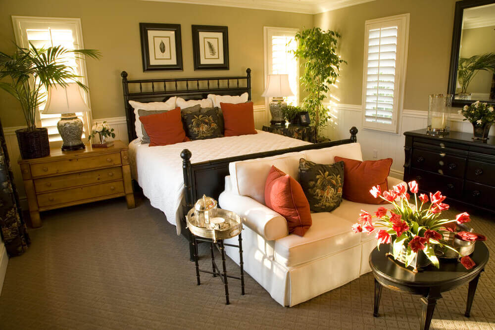 Professionally decorated master bedroom designs with a white loveseat, a massive bed with wooden frame and a dark wood headboard. There are plants in every corner and also flowers on the small coffee table.