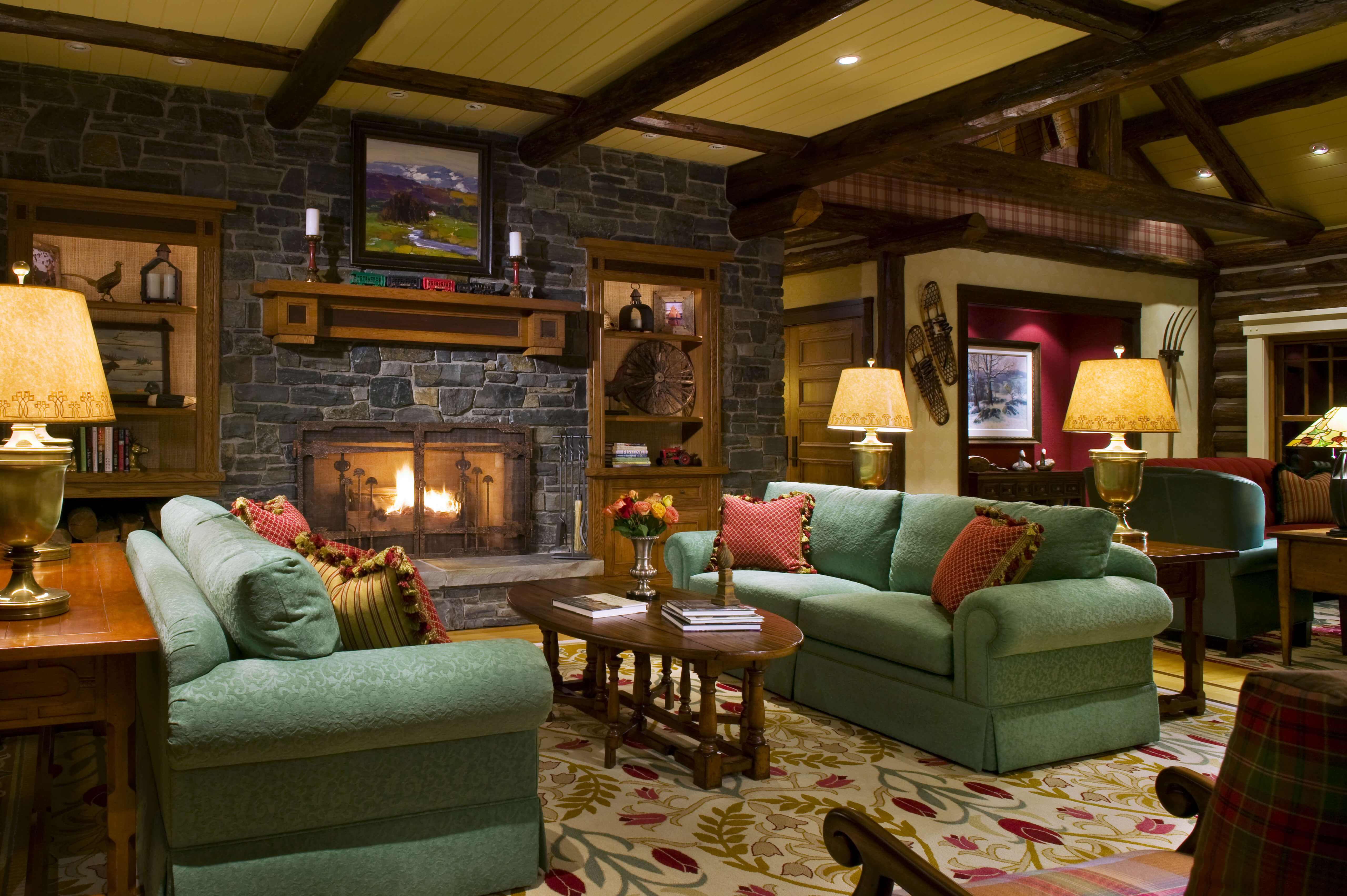 Rustic living rooms with turquoise sofas with red pillows, dark granite fireplace and sloped ceiling with light spots. A multi floral carpet with an oval wooden table coffee.