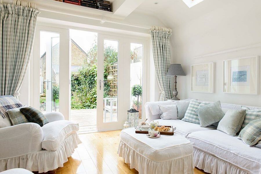 Shabby chic living rooms with white walls, white sofa, white coffee table and sloped ceiling. The room has a cozy design with with rustic accents. It has two large double doors that lead to the green garden.