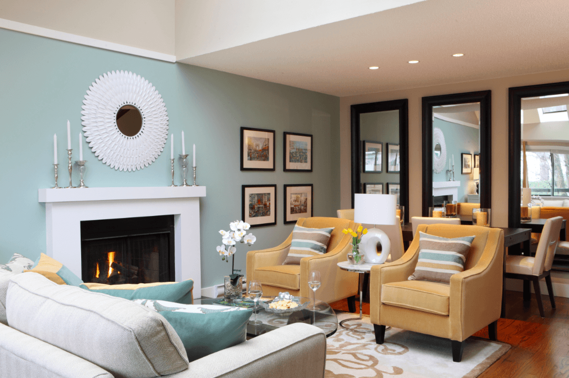 Small living room ideas with turquoise walls with three tall mirrors and a large white sofa with two chairs. Also a white fireplace with a coffee table made of glass.