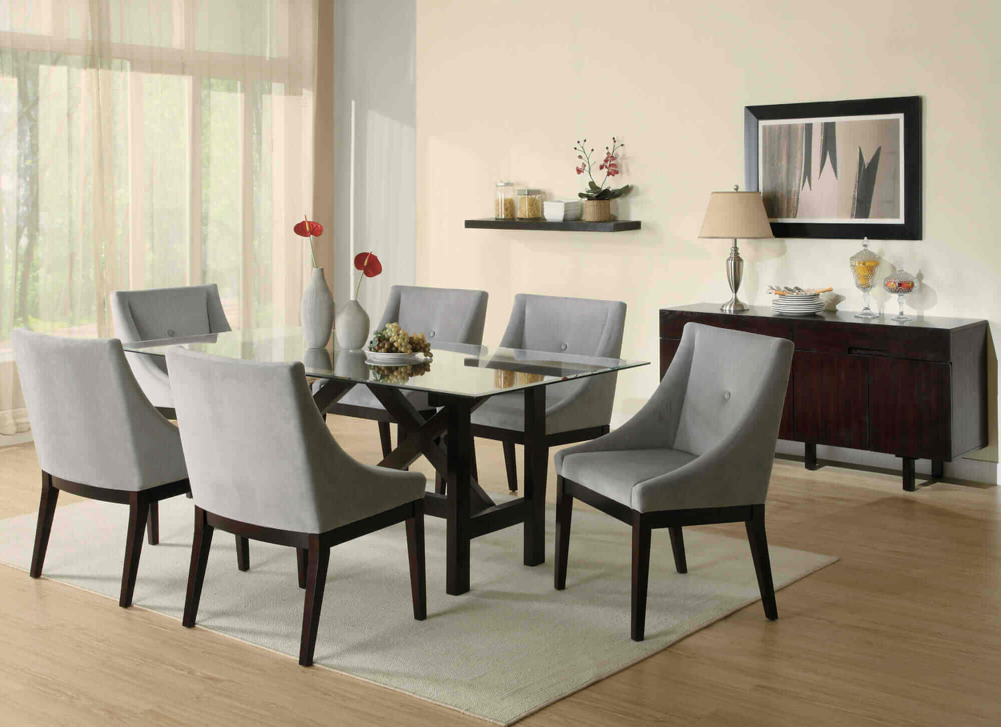Stylish dining rooms top designers - A small six chair table with a cozy design. The table is made of glass and the table and chairs feet are made of black wood. This is in contrast with the grey fabric and carpet.
