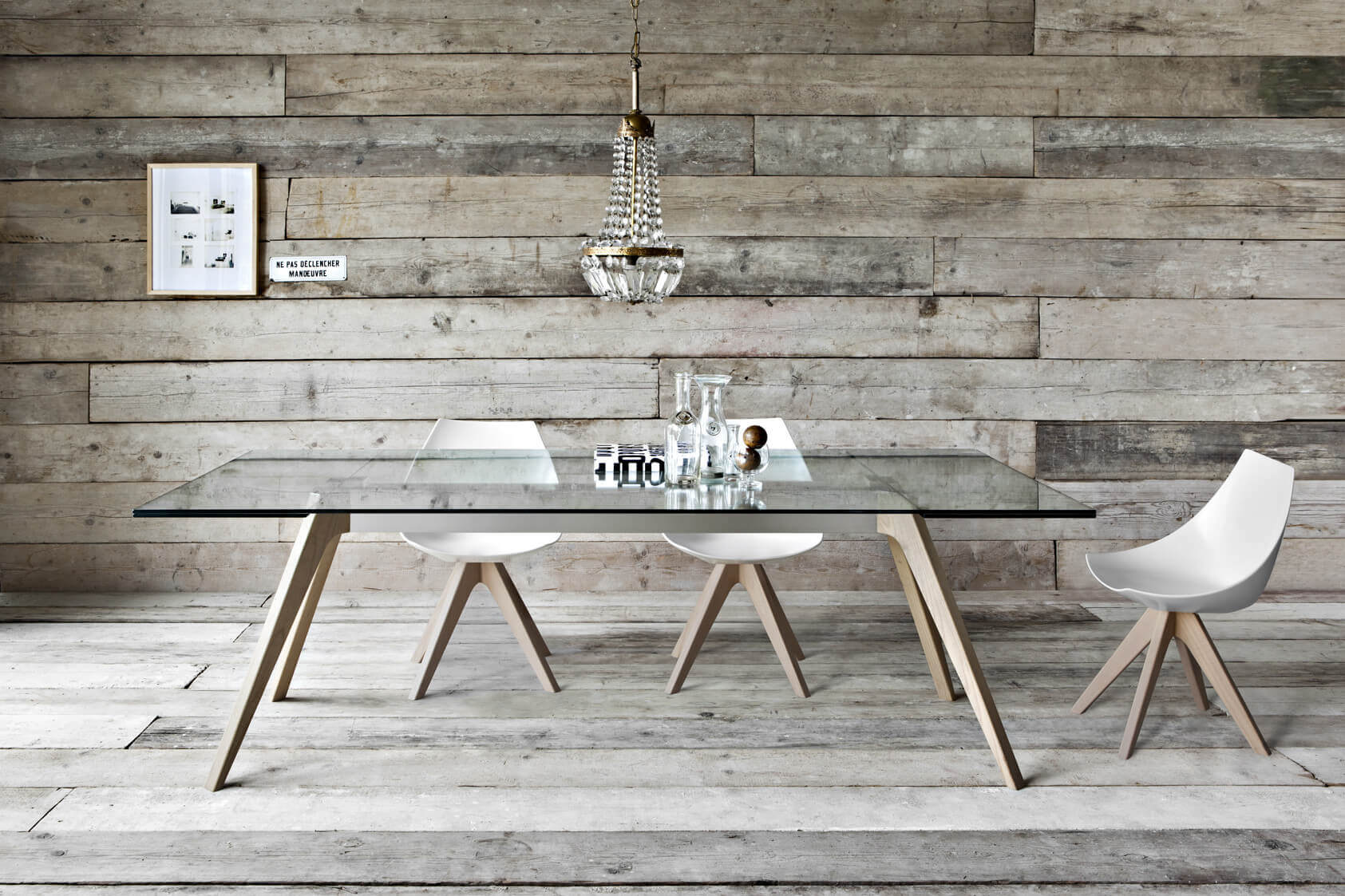This is one of the types of dining room tables that impress with simplicity. A modern table for six made of glass and with light color wood as feet. A small chandelier is placed up top the table. The walls are made of the same wood and in the same design as the floor for a grater visual effect.