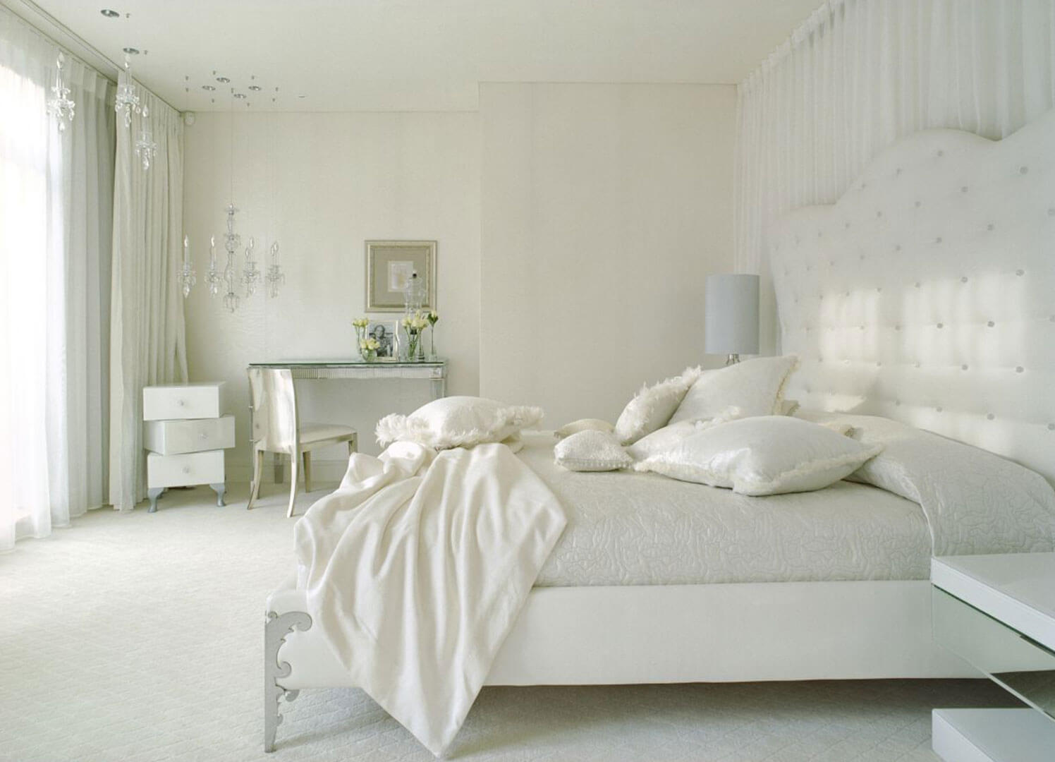 Brilliant white bedroom designs with white bed sheets, cabinets, chairs walls, drapes white curtains, pillows, white headboard. The only contrast is way that the furniture shade is cast on the ground.
