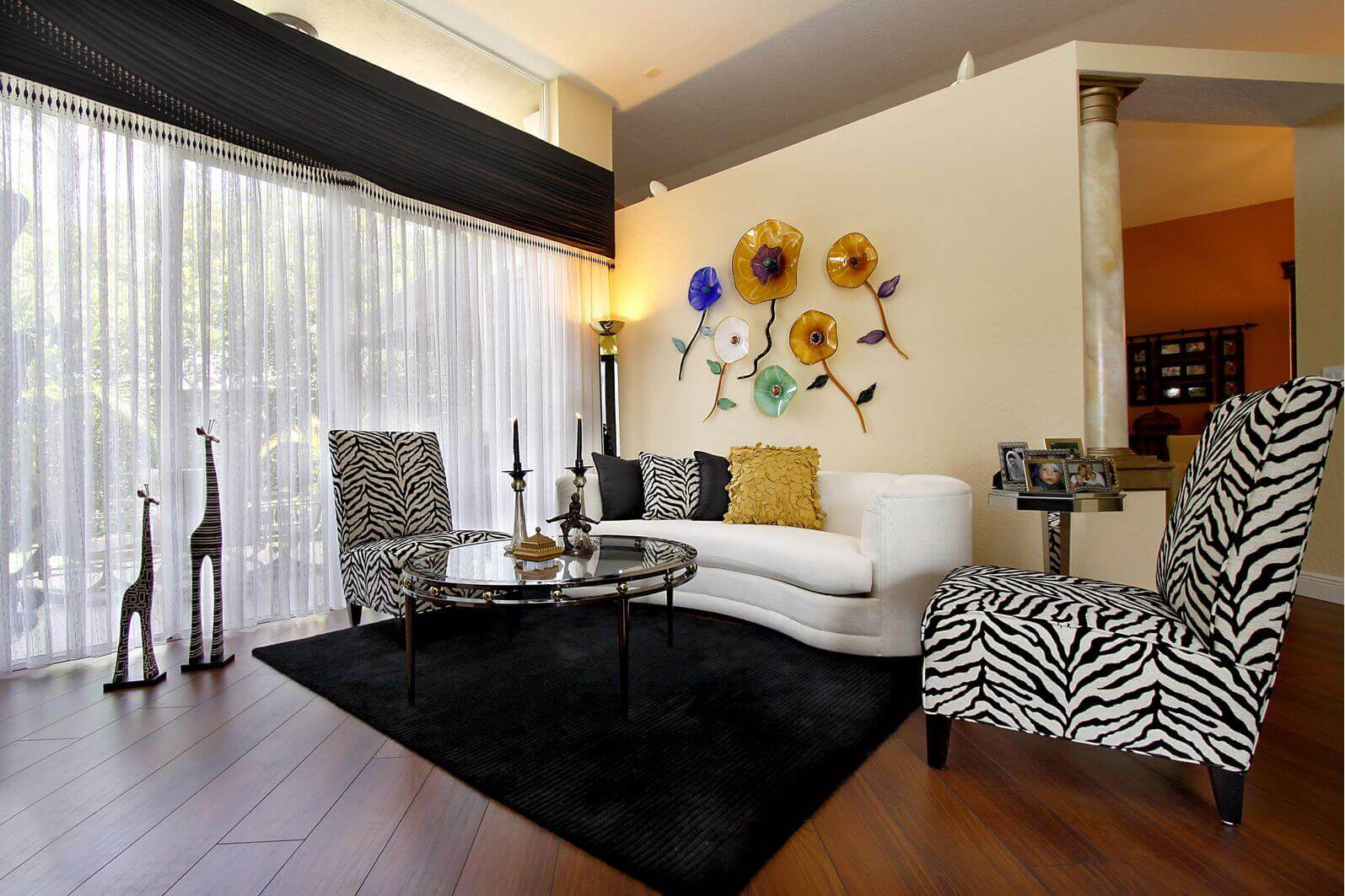 Zebra living room decor idea with chairs covered in zebra style fabric, zebra ornaments, black carpet over the dark brown floor, long and wide white drape, and a pillow with zebra motif.