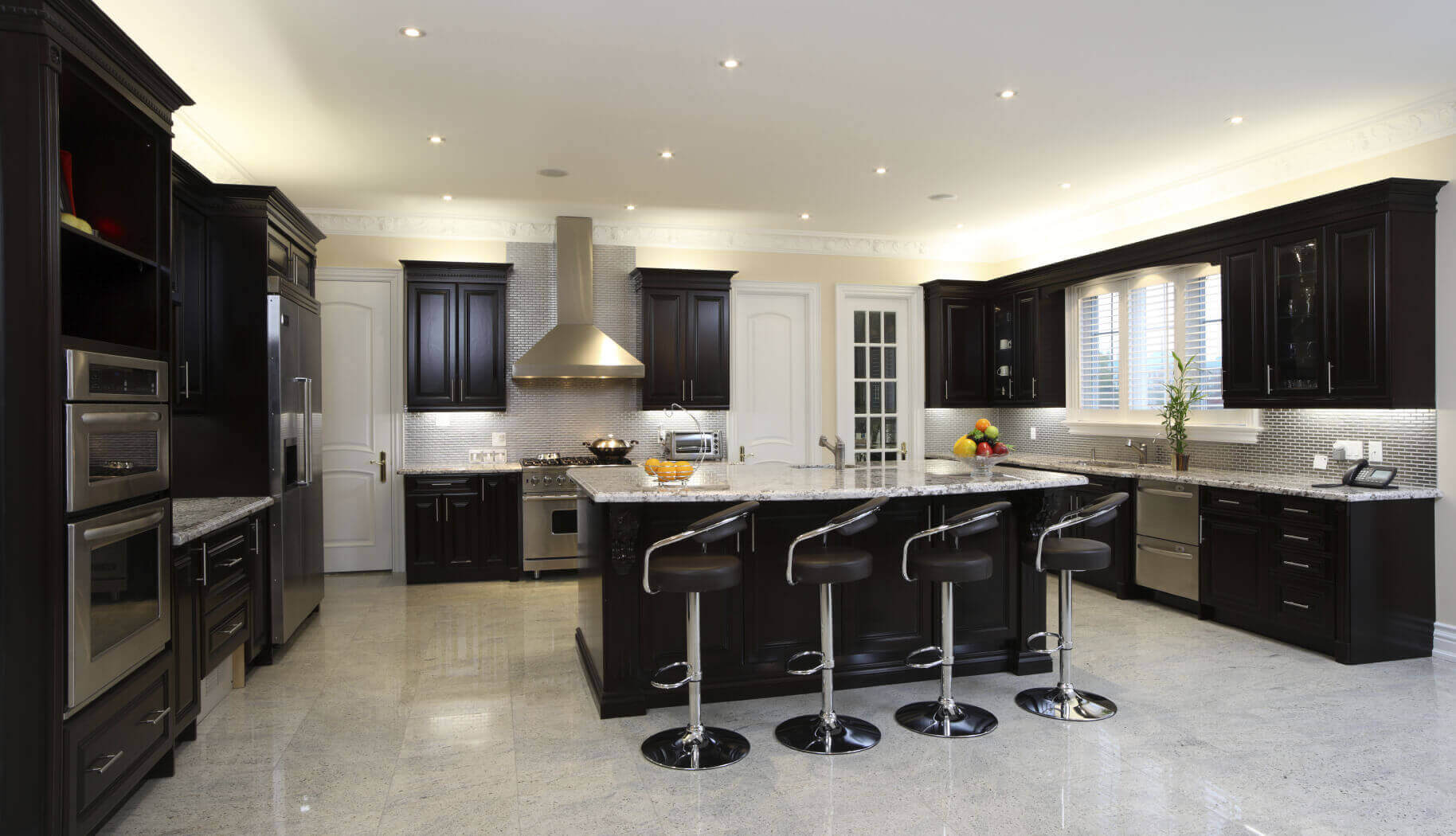 A contemporary black kitchen in a sleek building features glamorous shiny countertops, crisp white walls with black shelves and cabinets. This black kitchen design idea blends style and utility for a space that is not only cutting—edge but inviting