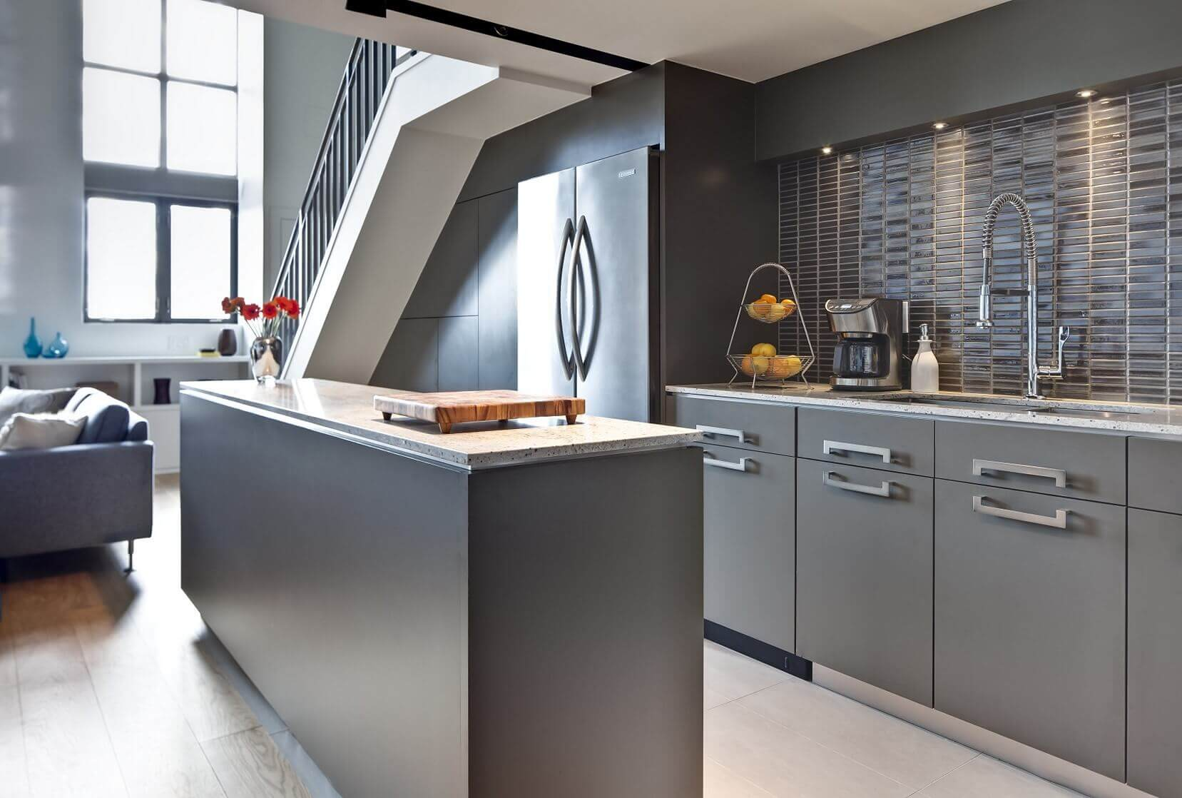 Bold contemporary gray kitchen cabinets add dimension and visual interest to this kitchen. All gray shelves, island with gray top, and stainless steel appliances complete the sleek design. The space beneath the stairs is useful for overflow storage and as a coffee bar.