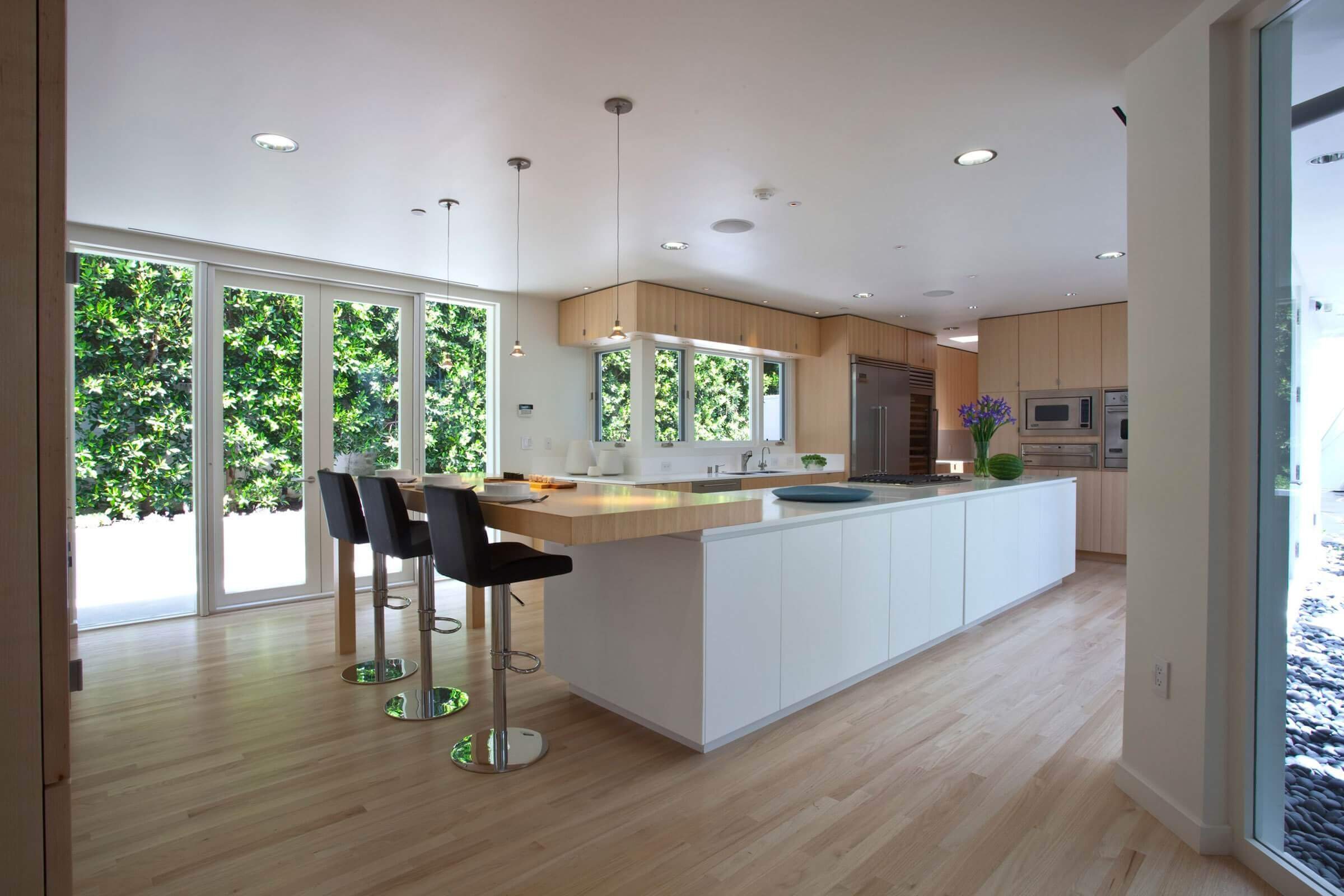 A large minimalist single–wall kitchen design with light brown cabinets, flat–panel cabinets, brown backsplash, stainless steel appliances, solid surface countertops, hardwood floors, and an eat–in island with contemporary kitchen breakfast bar stools
