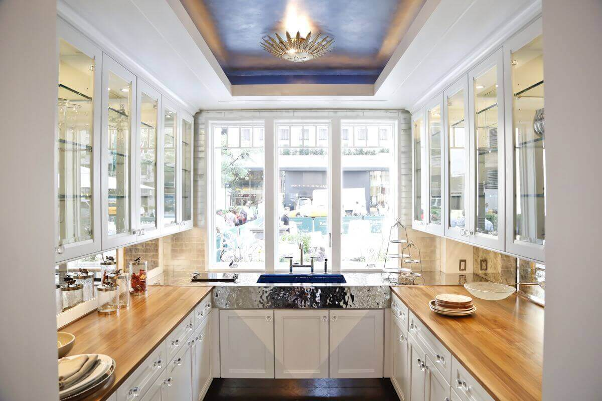 Mid–sized contemporary U–shaped kitchen idea with an undermount sink, white cabinets, contemporary kitchen cabinets glass doors, glass backsplash, wood countertops, medium toned hardwood floors, and stainless steel appliances