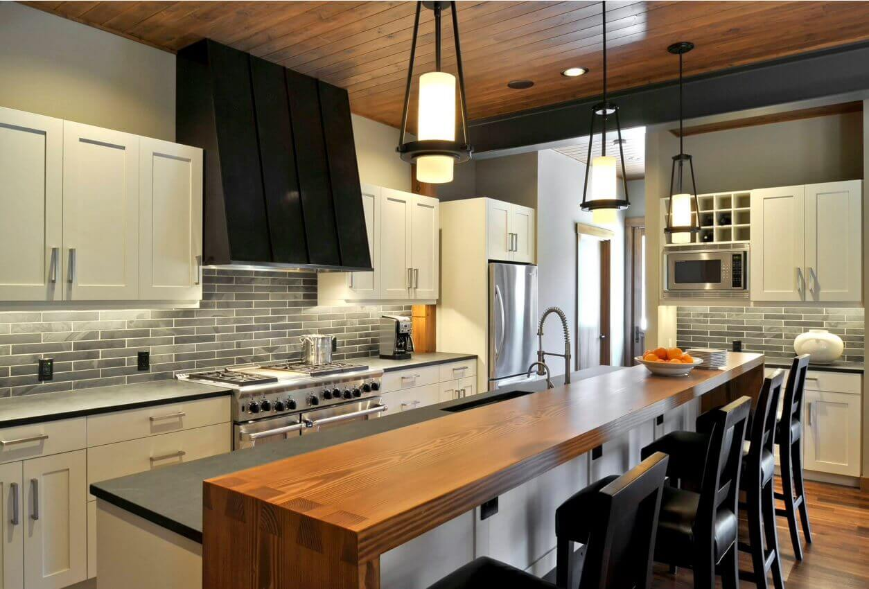 With its minimalist cabinetry, metallic accents, and gray–and–black brick backsplash, this contemporary kitchen design has a subtle elegance for small spaces that will never go out of style