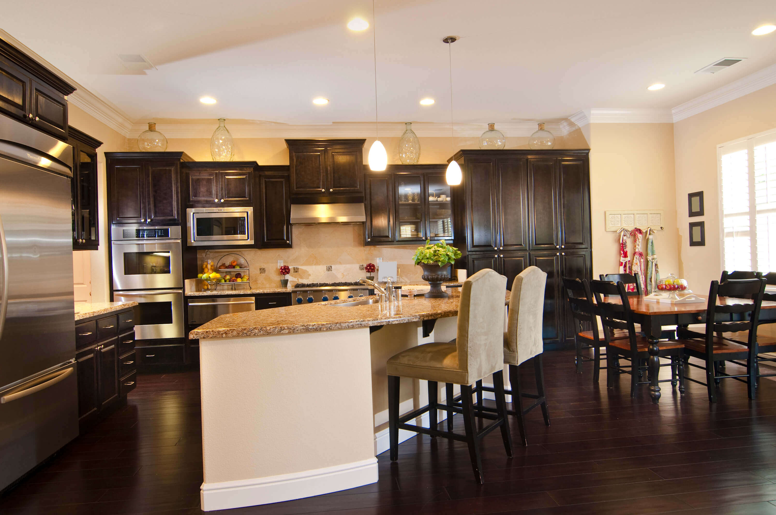 Rich chocolate brown cabinets add beautiful contrast to this contemporary kitchen. Stunning cream granite tops the counters as silver appliance, modern granite backsplash, and hardwood floors completes the sleek look of this awesome contemporary kitchen design idea