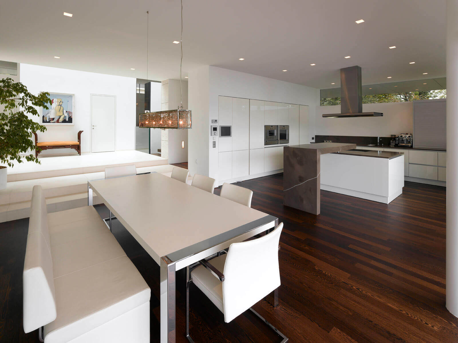 Contemporary kitchen family room ideas is now trendy for those who want a relaxing place for their family while the next meal is prepped. The dark wooden floor harmonizes perfectly the white armless sofa and walls of this kitchen