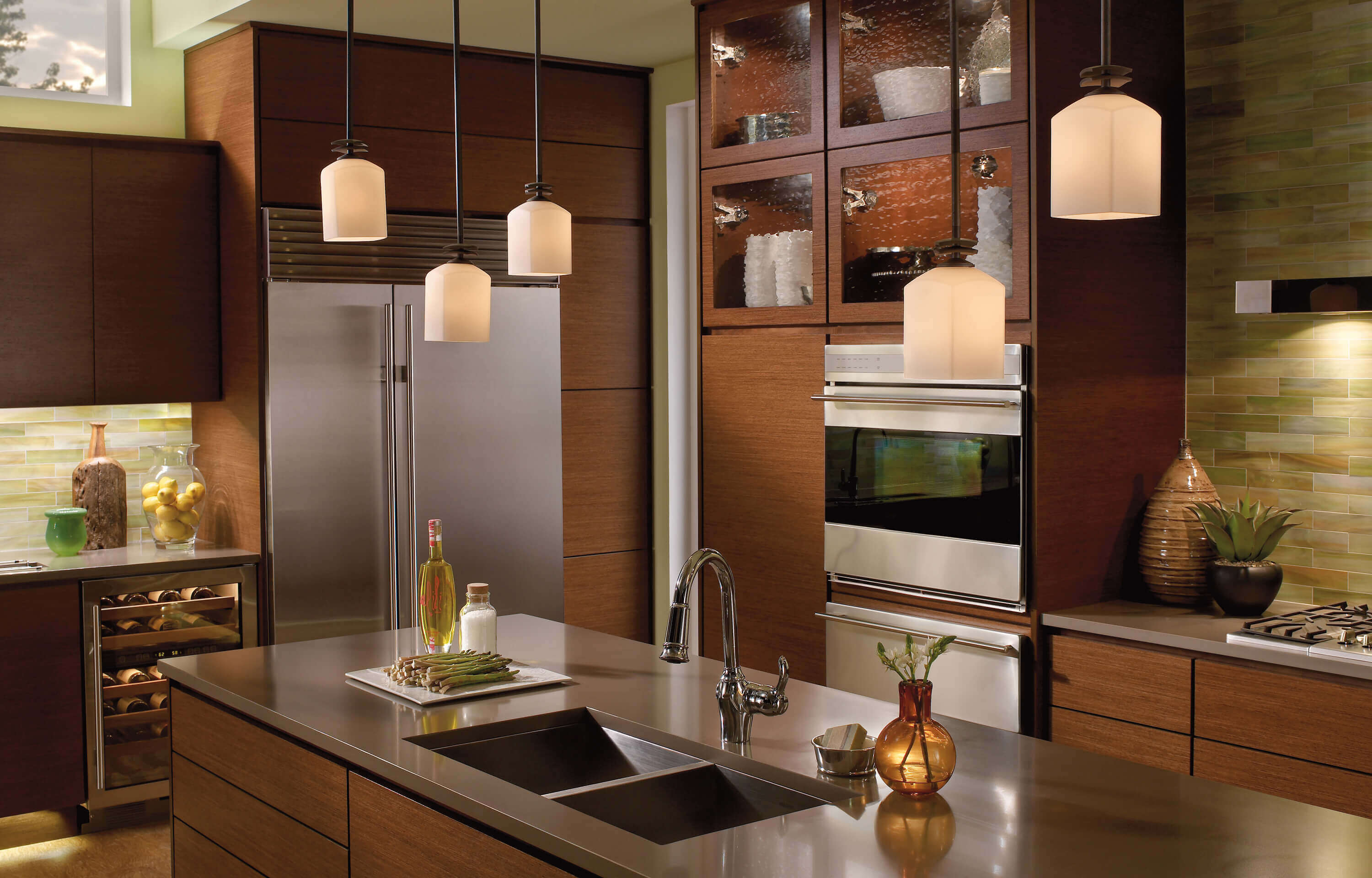 A small spaced kitchen design with a contemporary kitchen sinks undermount, flat–panel cabinets, dark wood cabinets, stainless steel countertops, stainless steel appliances, and an island with pedantic light, brick backsplash