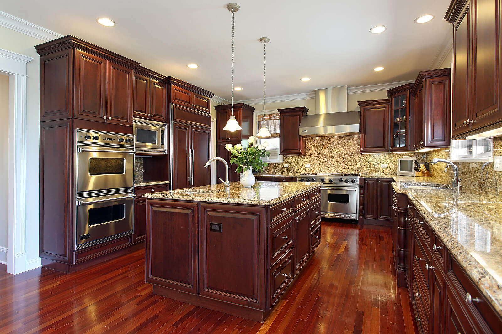This elegant contemporary kitchen takes its color inspiration from nature. It features brown cherry cabinets, cream granite backsplash, crisp white walls and ceiling, and a stainless steel cooktop well positioned in between the cabinets
