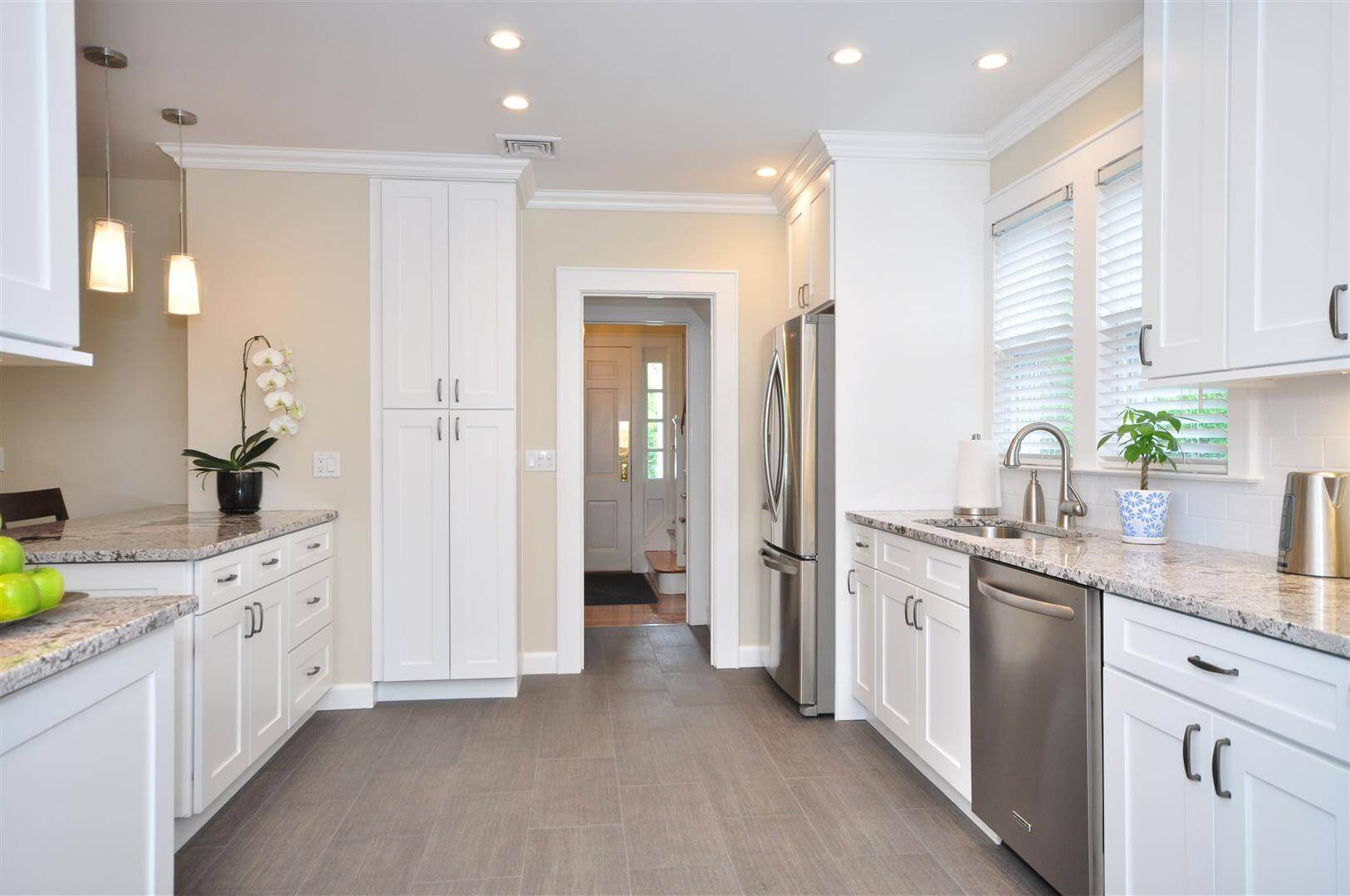 Crisp white cabinetry pairs with granite countertops and milk wall in this contemporary kitchen design. White pendant lights feature stainless steel cords and other stainless steel appliances add fun pattern and interest to the space