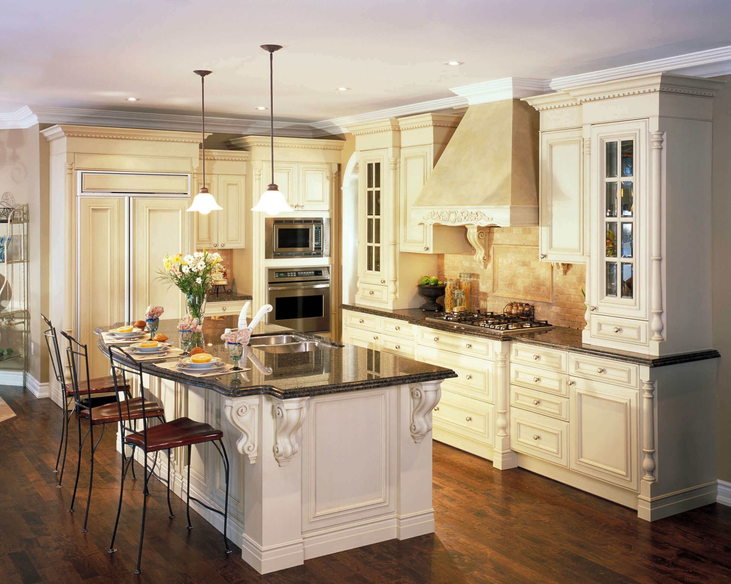 The marble countertops, white cabinets and two contemporary pendant lighting for kitchen give this contemporary kitchen space an elegant feel. The stainless steel appliances and fine wooden floor lend an updated look