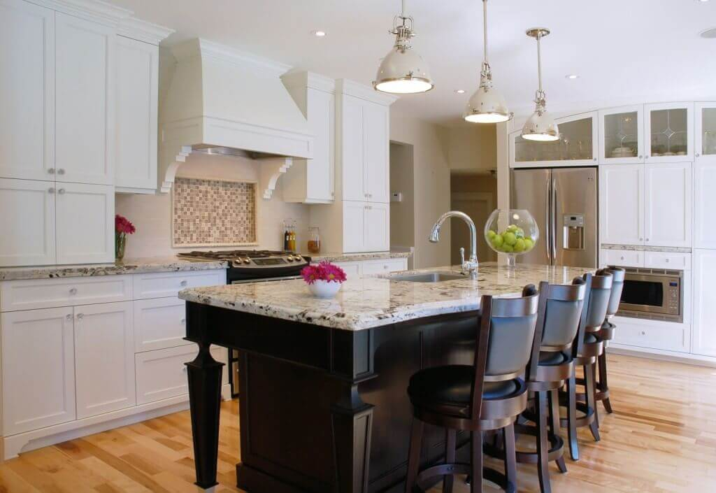 The chic metallic orb kitchen island pendant lighting fixtures emphasize the heft and scale of this polished black kitchen island. A light marble countertop and stunning rustic bar chairs keep the silhouette sleek