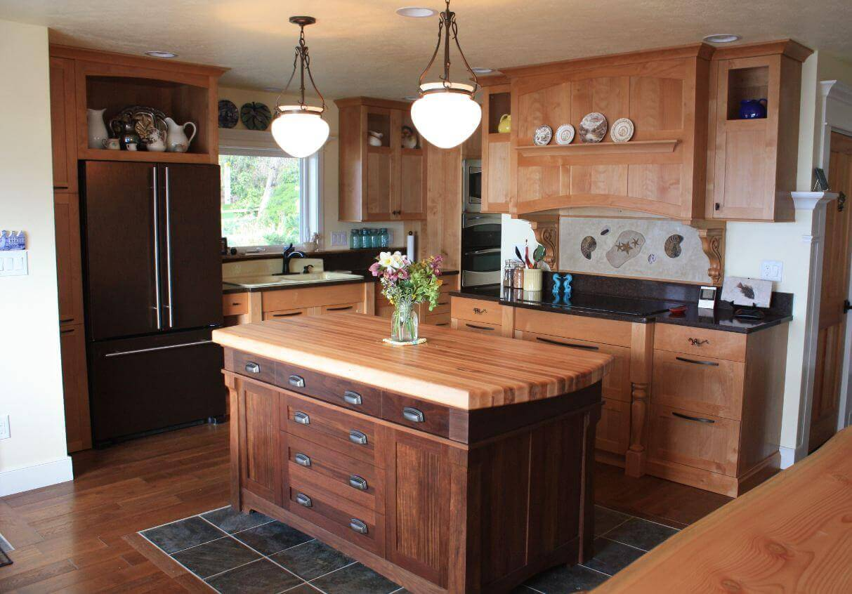 This small kitchen island with butcher block top has clean and traditional lines. The island base matches existing décor, while the butcher block top adds visual interest. The island seated on dark tiled flooring that provides visual contrast to the whole space