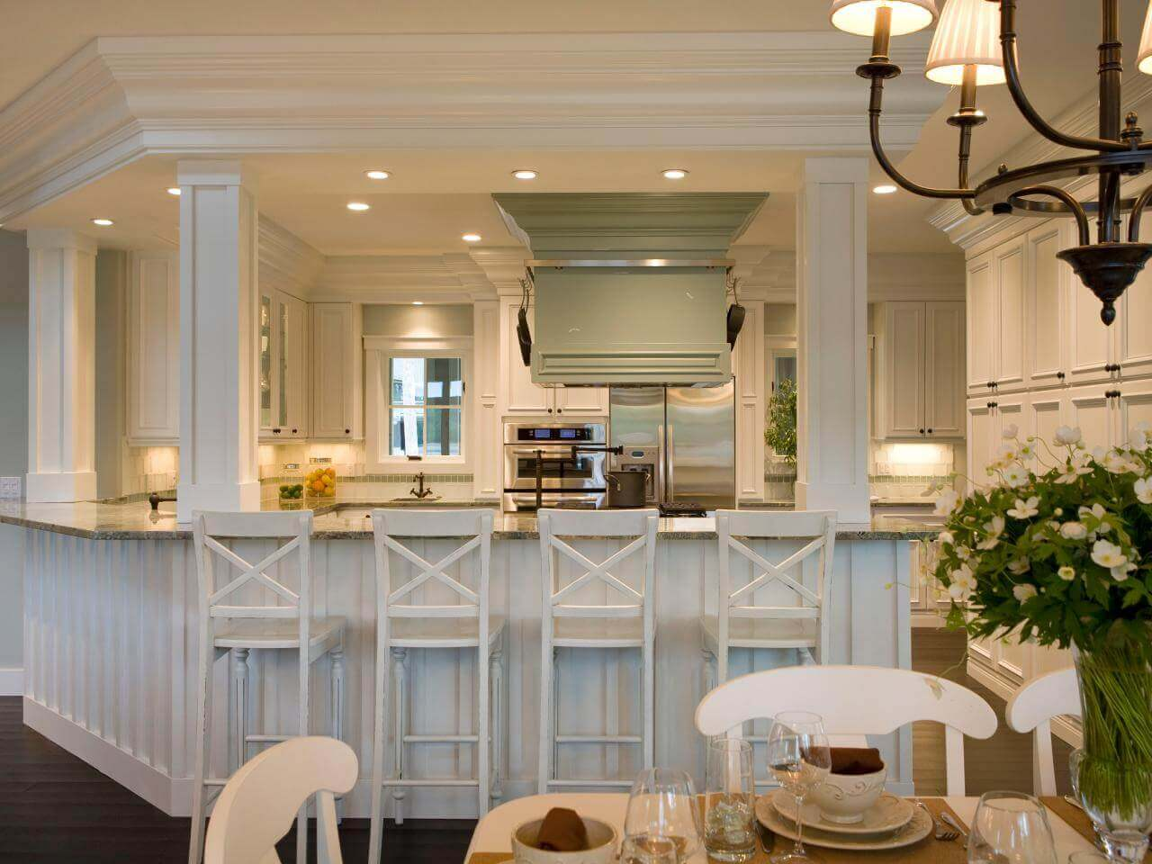 While it looks polished and modern, this white kitchen island with columns and seating for four makes a great deal of the space. Building the island with the columns ensures that wasted space is minimized