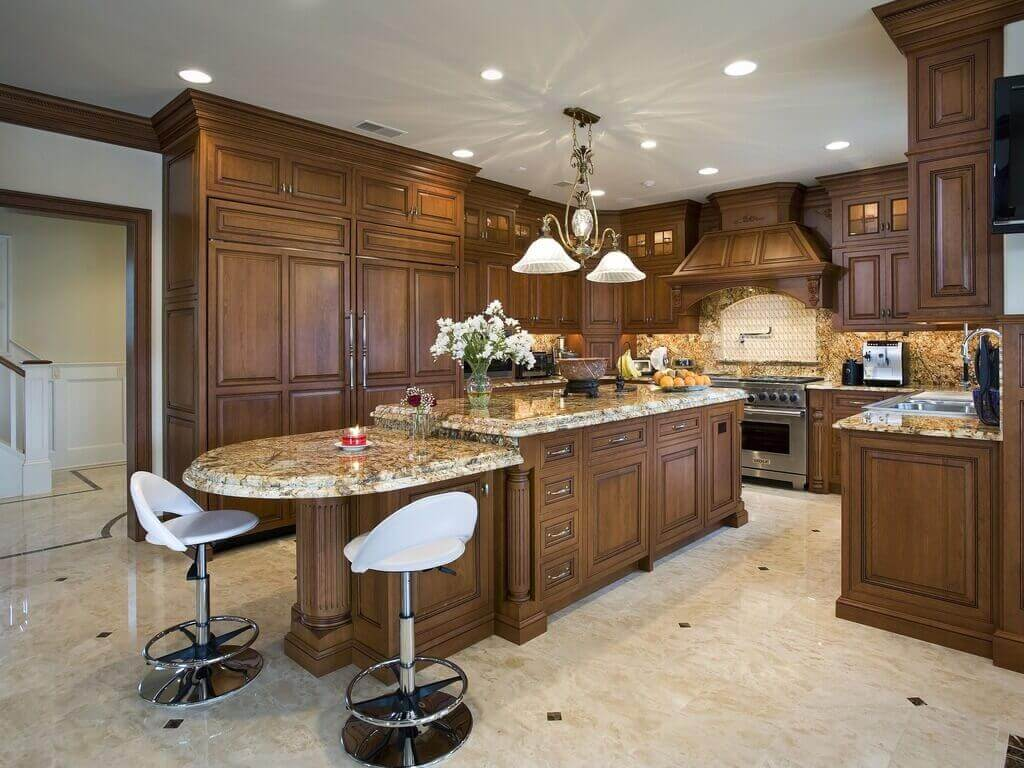 The above kitchen features a two–tiered mid–size modern kitchen island with seating for two that combines a sleek design, medium brown colors, and natural materials. The two modern barstools add utility, and warmth