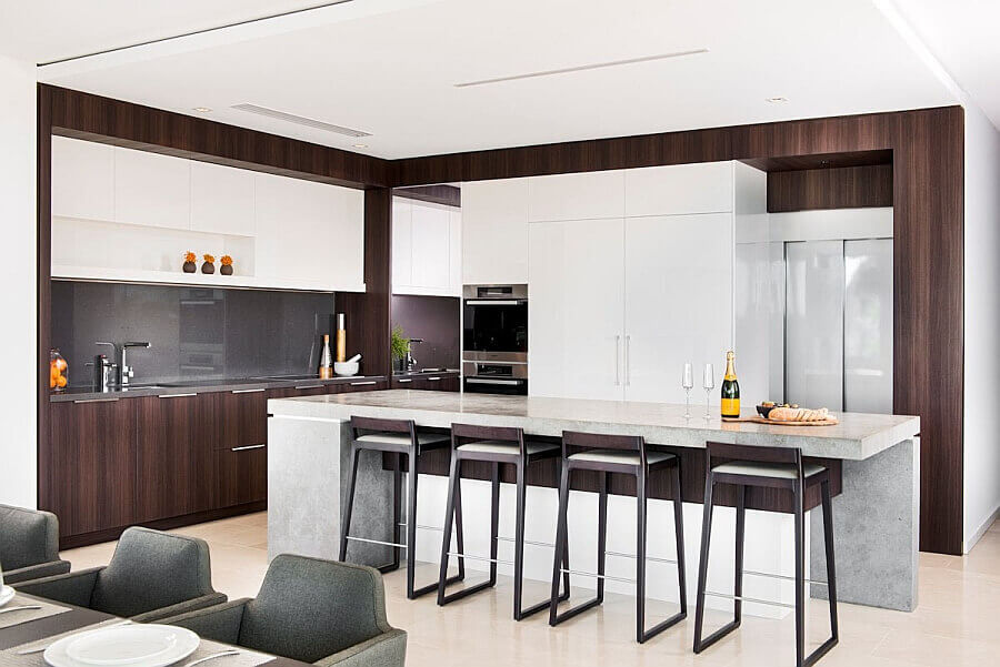 A glossy top and perfect styling give this unique all marble kitchen island with stools underneath a simple no fuss look. Four stylish stools are tucked away beneath the countertop