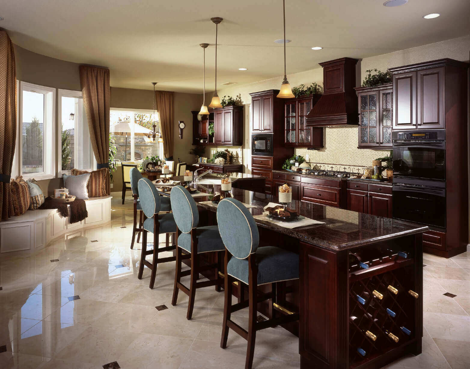 This expansive kitchen island with wine rack features a built–in sink and a broad dark marble countertop. It houses plenty of in–kitchen dining space on the marble countertop and a large wine rack