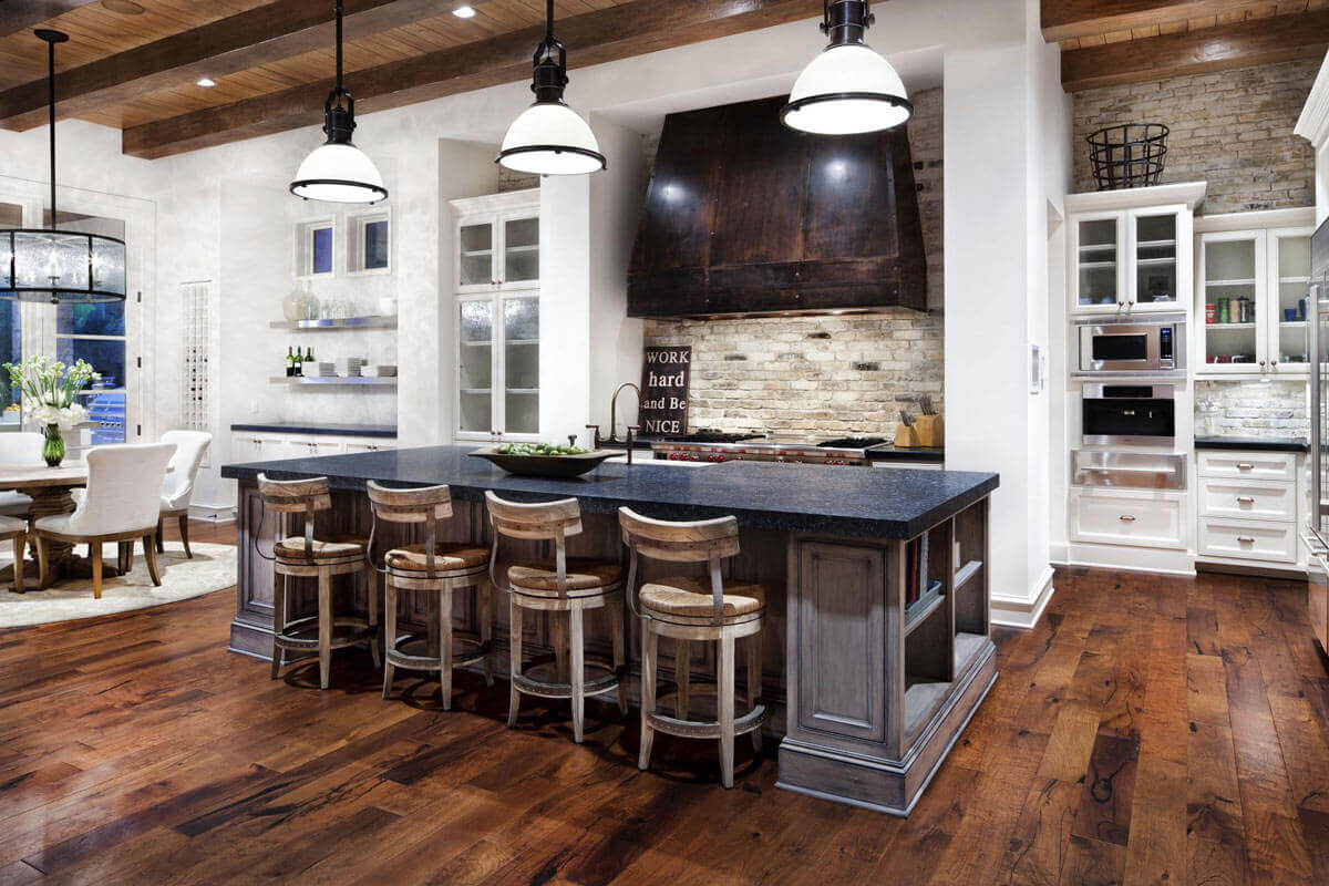 This country kitchen island with breakfast bar is designed to seat four comfortably. Four rustic bar stools add charm to the space. A dark granite countertop provides plenty of dining space