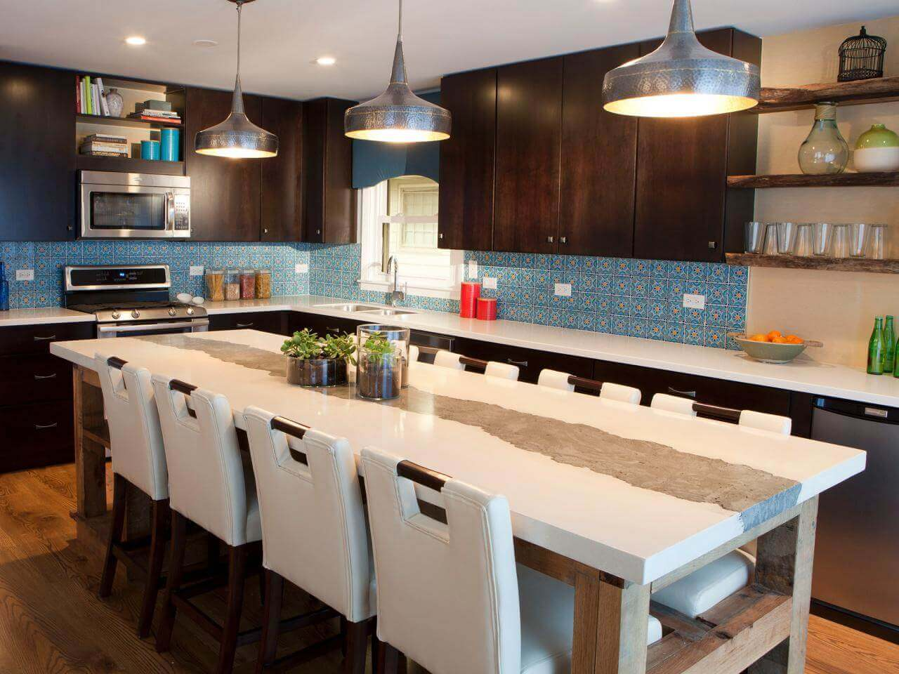 The kitchen above features a large kitchen island idea with plenty in–kitchen eating space and seating options. With white countertop, medium brown wood legs, and artistic craftsmanship, it combines natural colors with natural materials, and a sleek design