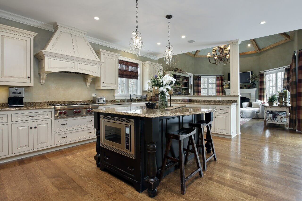 A kitchen in white and medium tone brown looks clean and sleek. Equipped with luxury kitchen appliances and an exquisite kitchen island, the kitchen is fabulously designed to satisfy even the most demanding of home chefs