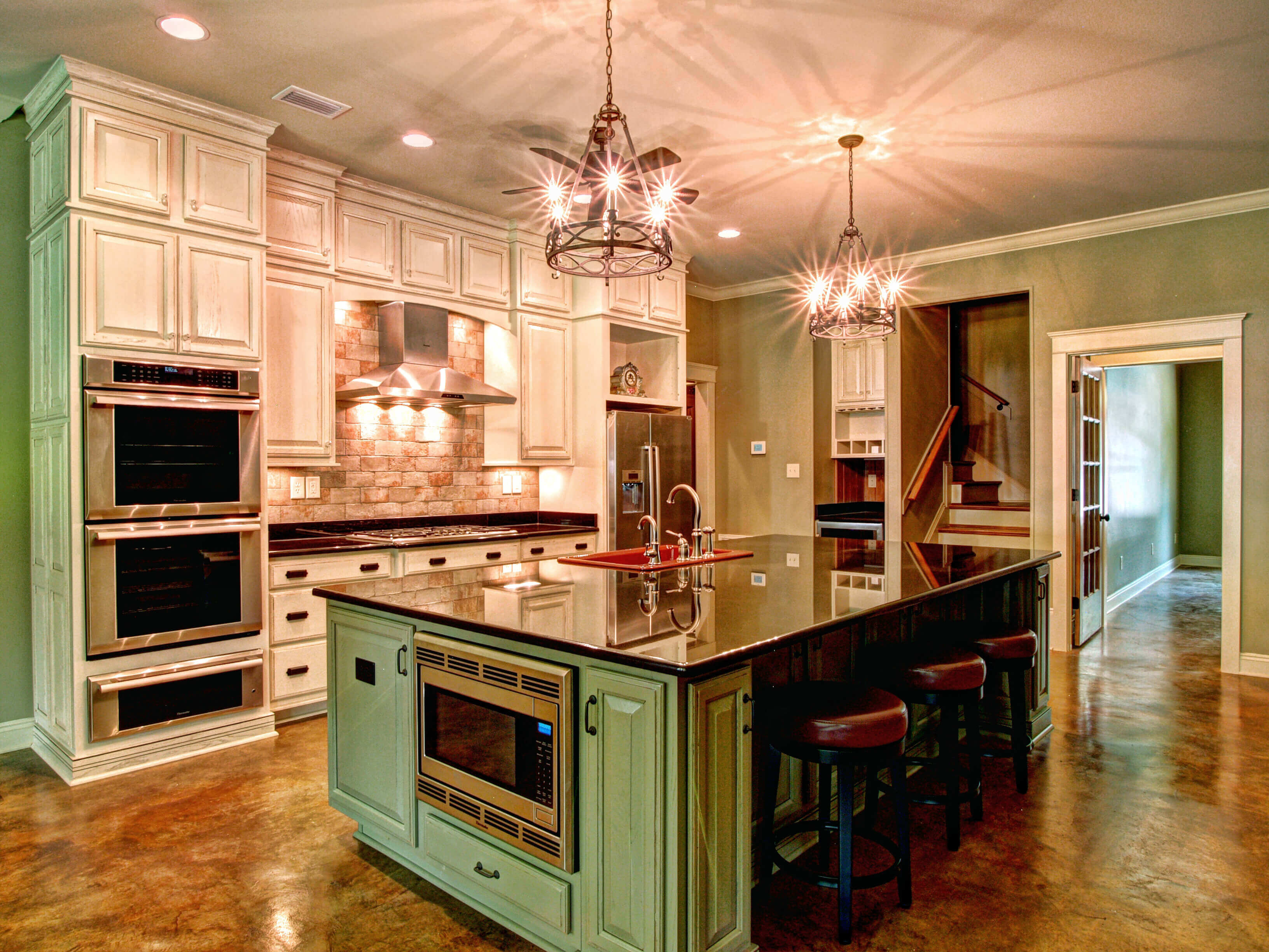 White cabinets, aluminium appliances, marble countertops, and luxury kitchen backsplash pictures are put together to create a homely kitchen design. Under hood lighting, pendant and recessed lighting fixtures provide brightness in the otherwise dark room