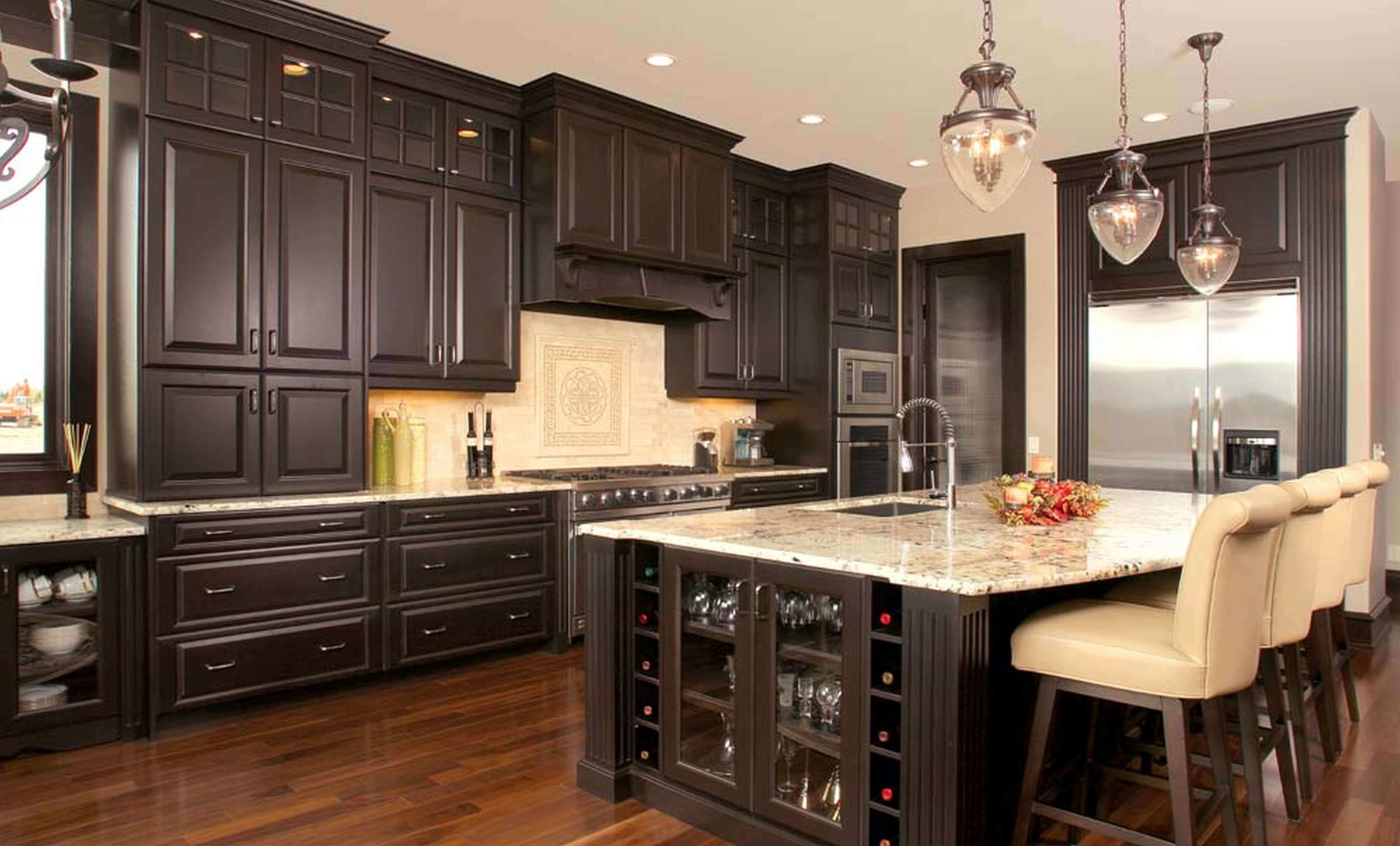 Dark oak cabinetry paired with luxury kitchen cabinet hardware builds an aesthetic fundamental for this room. Materials such as stainless steel, cream tile backsplashes and bright granite countertop further accent the elegance of the space