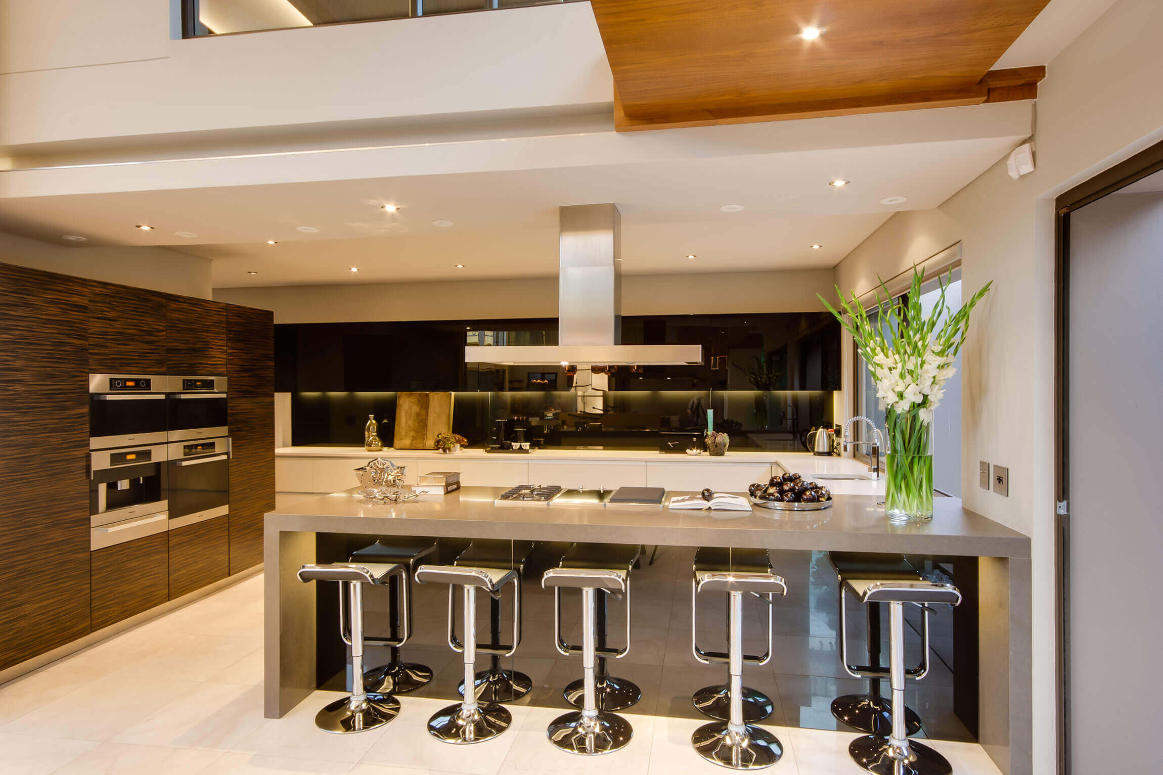 This long, fabulous kitchen island ties in perfectly with the feel of the room. The light gray color scheme of the island, luxury kitchen counter stools, and grained dark wood cabinets extend the modern look of the kitchen